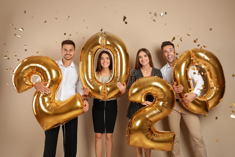 Happy young friends with golden 2020 balloons on background. New Year celebration stock photos