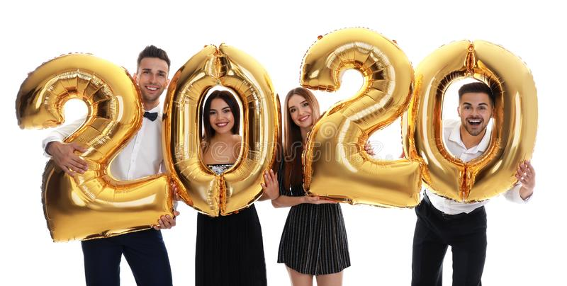 Happy young friends with golden 2020 balloons on white. New Year celebration stock photo