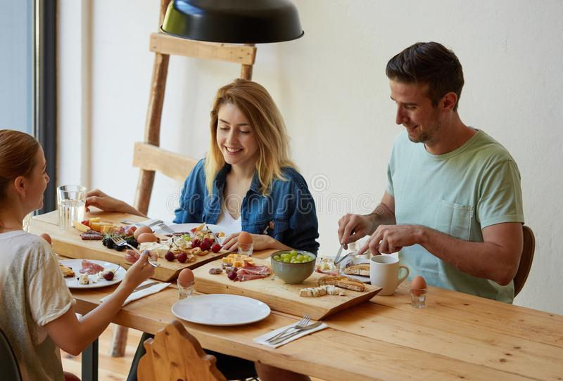 Happy young friends having breakfast royalty free stock image