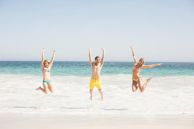 Happy young friends jumping on the beach royalty free stock photography