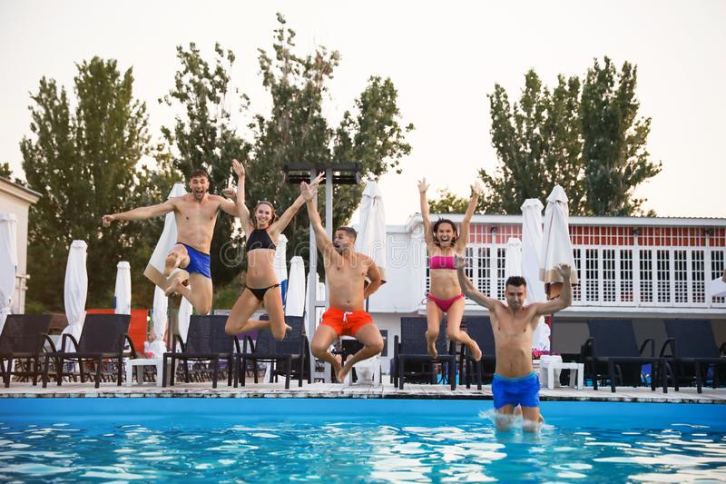 Happy young friends jumping in pool royalty free stock photos