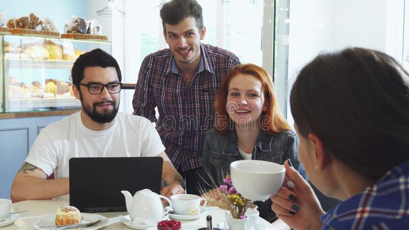 Happy young friends laughing, enjoying having coffee together royalty free stock photography