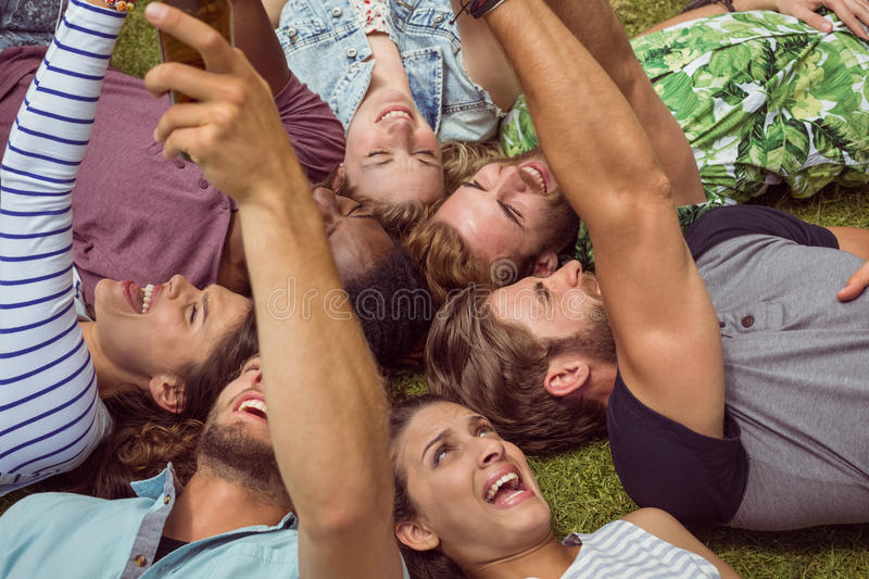 Happy young friends lying on grass stock photos
