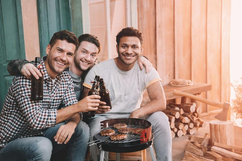 happy young friends making barbecue and drinking beer on porch stock photo