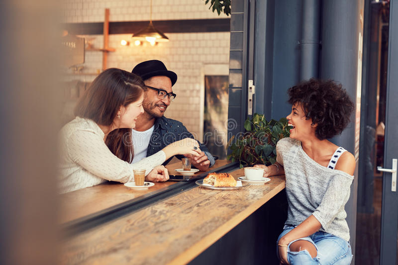 Happy young friends meeting in a coffee shop royalty free stock image