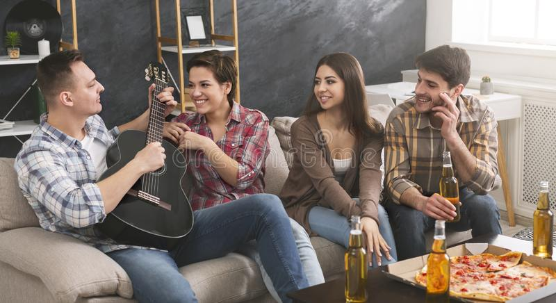 Happy young friends playing guitar, spending time together royalty free stock photography