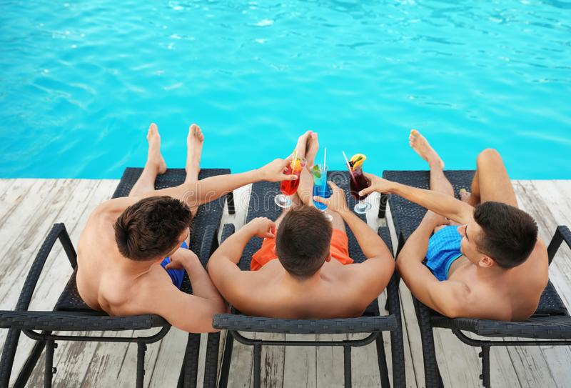 Happy young friends with refreshing cocktails relaxing on deck chairs near pool royalty free stock images