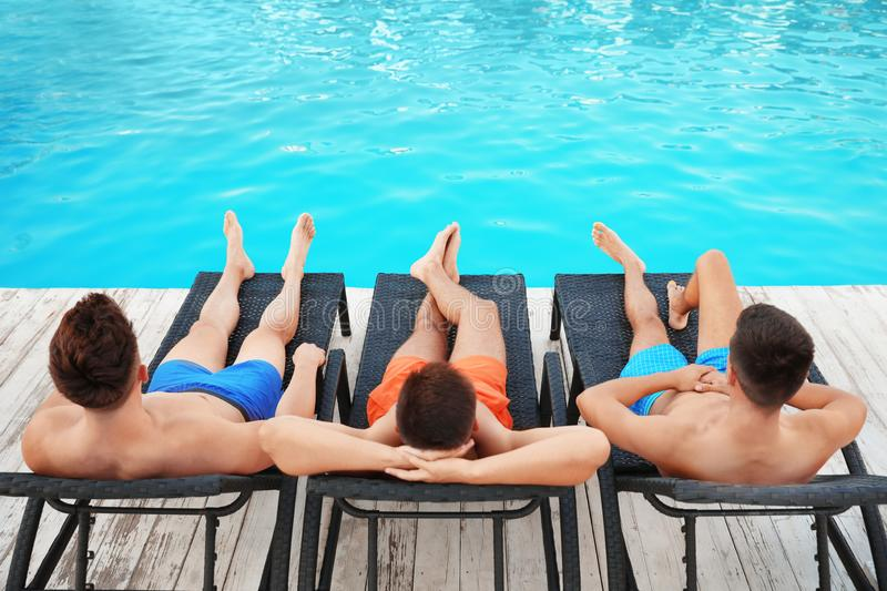 Happy young friends relaxing on deck chairs stock photos