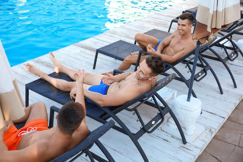 Happy young friends relaxing on deck chairs near  pool royalty free stock photo