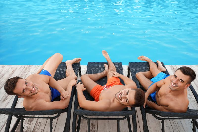 Happy young friends relaxing on deck chairs royalty free stock photos