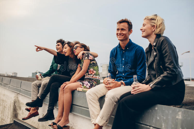Happy young friends relaxing on rooftop. Shot of young men and women sitting on terrace. Friends relaxing on rooftop royalty free stock images