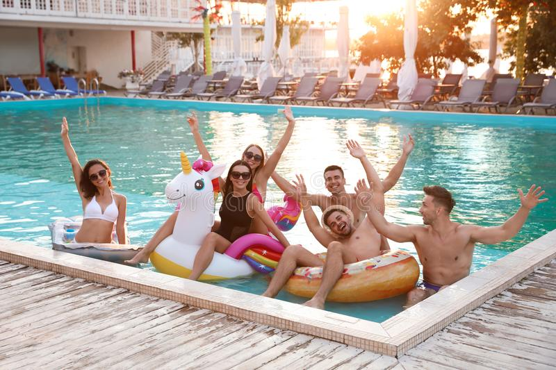 Happy young friends relaxing in pool royalty free stock images