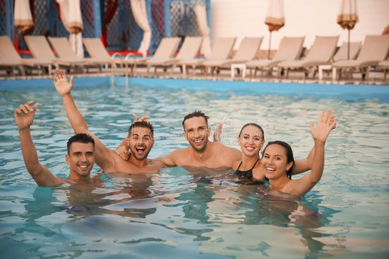 Happy young friends spending time in pool royalty free stock image