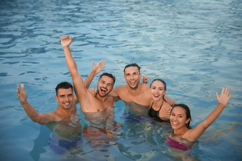 Happy young friends spending time in pool royalty free stock photography