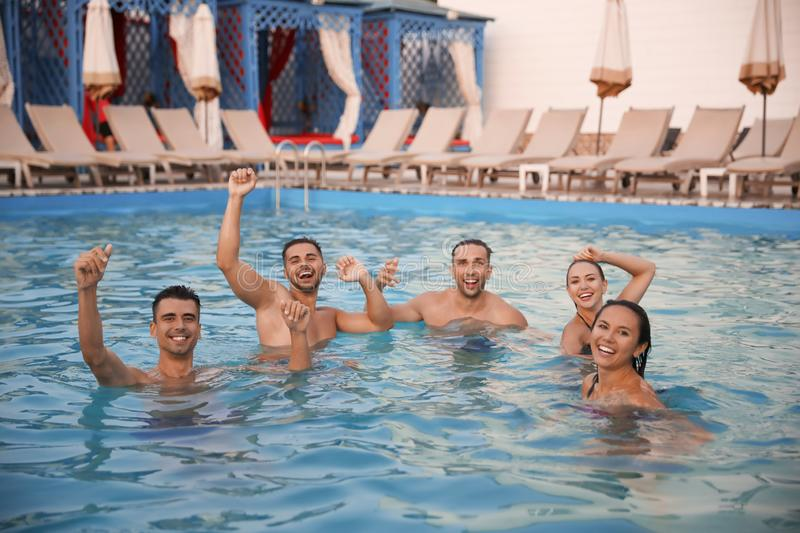 Happy young friends spending time in pool royalty free stock images