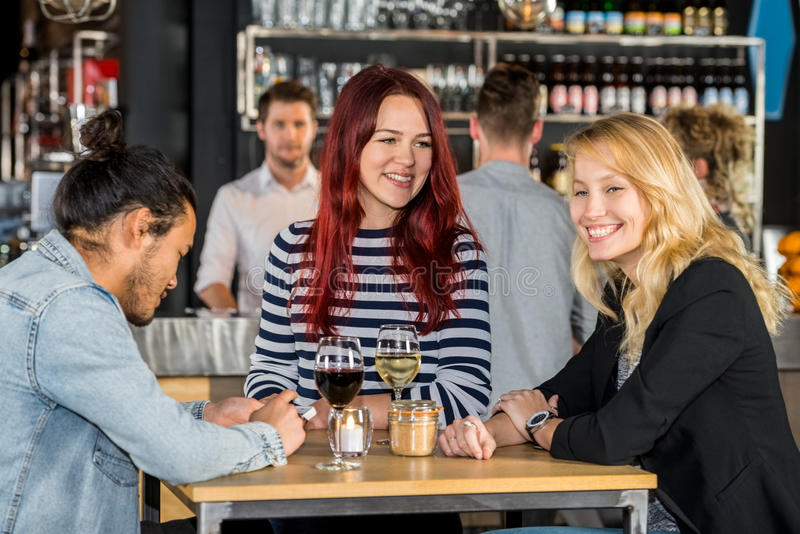 Happy Young Friends At Table In Restaurant. Smiling young women with male friend at table in restaurant royalty free stock photography