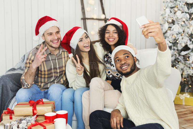 Happy young friends taking Cristmas selfie photo royalty free stock photography
