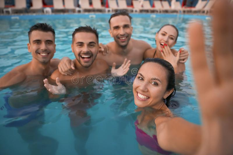 Happy young friends taking selfie in pool stock image