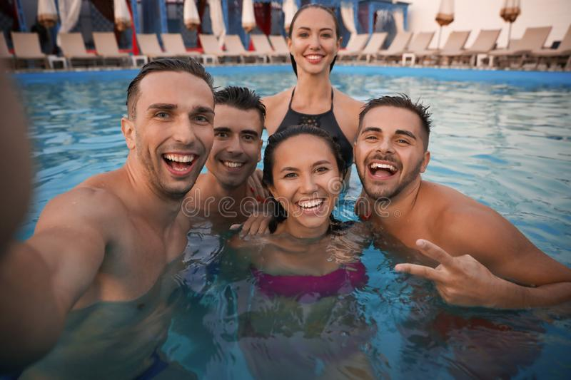 Happy young friends taking selfie in pool royalty free stock photography
