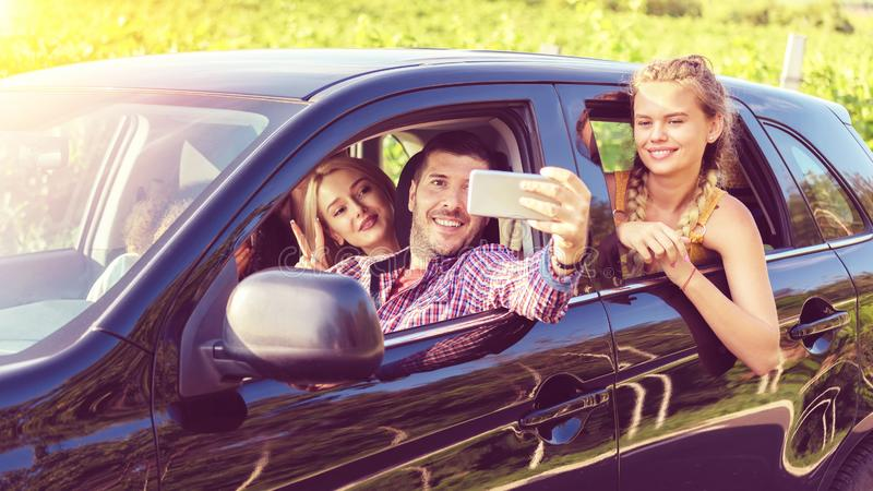 Happy young friends taking selfie while traveling together by car at countryside royalty free stock photography