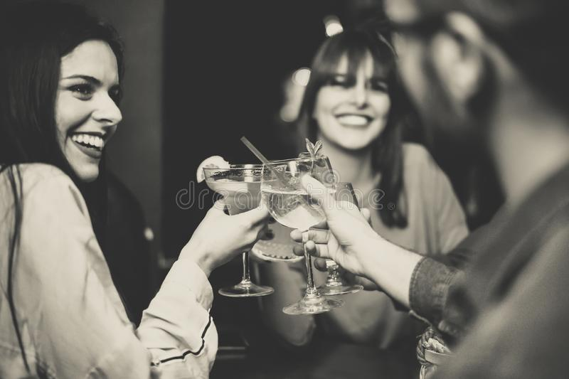 Happy young friends toasting and cheering cocktails at disco bar - Multiracial people having fun enjoying drinks at club stock image