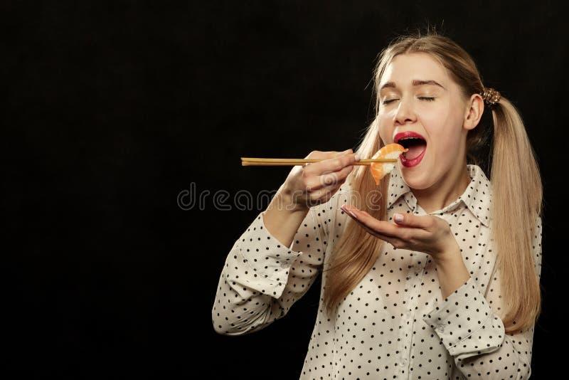 Woman eats sushi stock photos