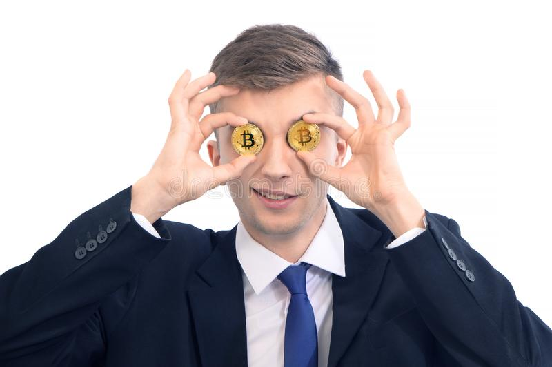 Happy young funny attractive businessman trader holding bitcoin cryptocurrency instead of eyes, isolated on white royalty free stock photos