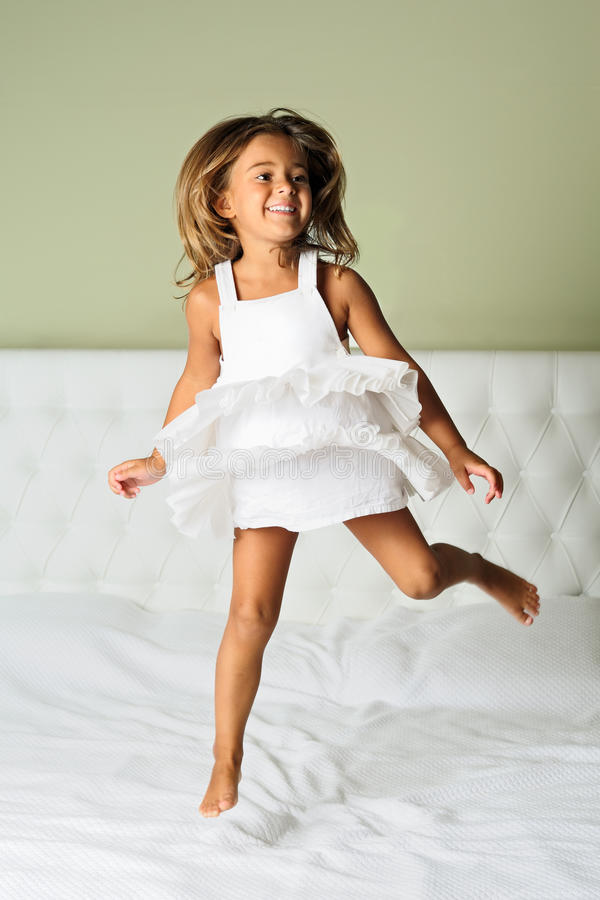 Happy young girl. A happy cute young girl in white dress having fun jumping on bed royalty free stock photos