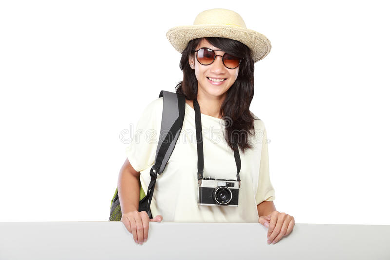 Happy young girl with backpack showing blank board stock photo