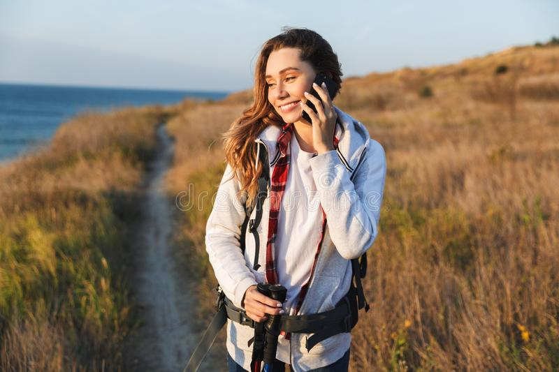 Happy young girl carrying backpack. Hiking, talking mobile phone stock photos