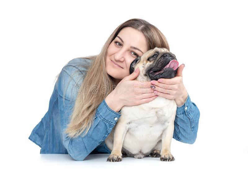 Happy young girl cuddles and hugs pug dog, isolated on white background stock photo