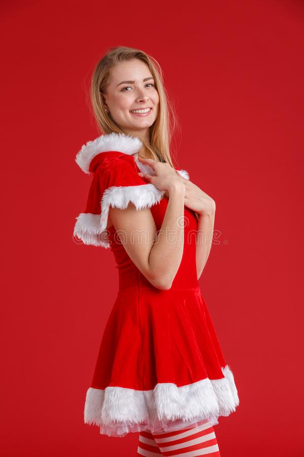 A happy girl in a Christmas dress stands sideways, smiling and holding her hands on her shoulders. royalty free stock photos