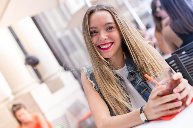 Happy young girl drinking a cocktail royalty free stock image