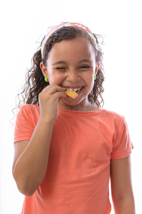 Happy Young Girl Eating Biscuit royalty free stock image