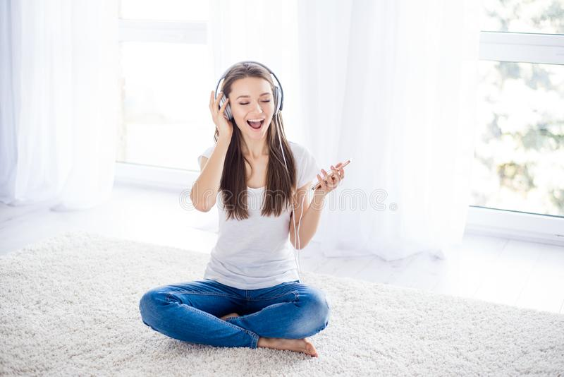 Happy young girl is enjoying listening to the music with headphones at home on white background royalty free stock photo