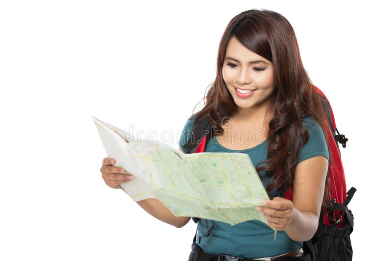 Happy young girl going on vacation with backpack and map. Portrait of happy young girl bring backpack and looking at the map stock image