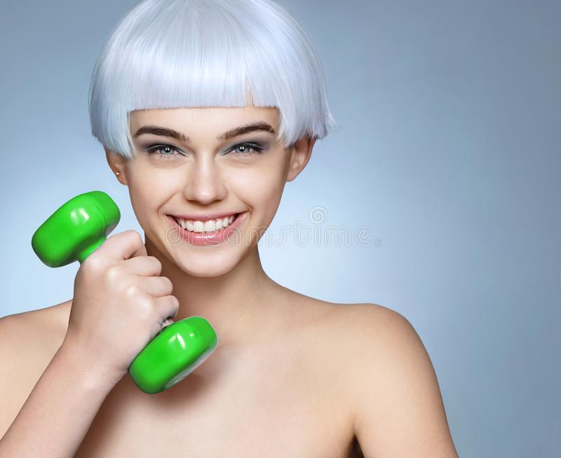 Happy young girl with green dumbbell in her hand. stock images