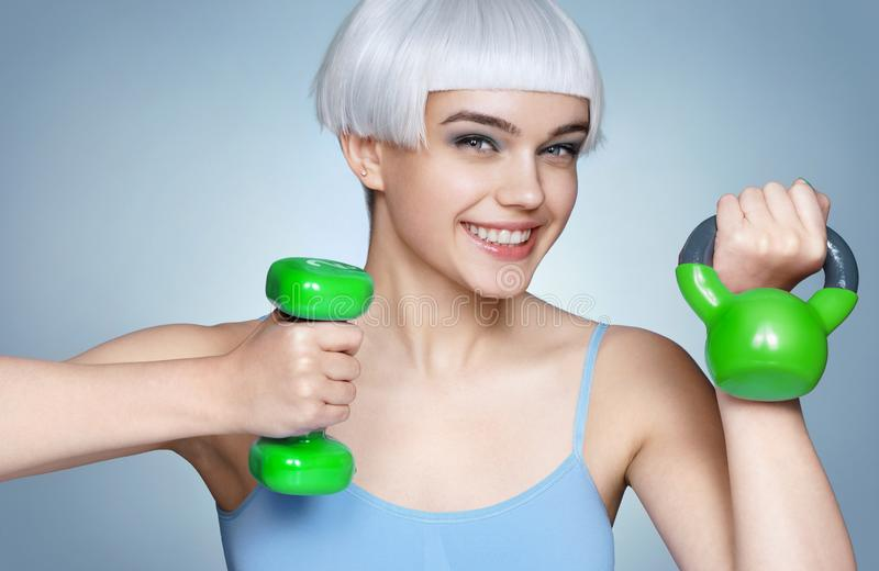 Happy young girl with green dumbbell and kettlebell in her hands. royalty free stock photography
