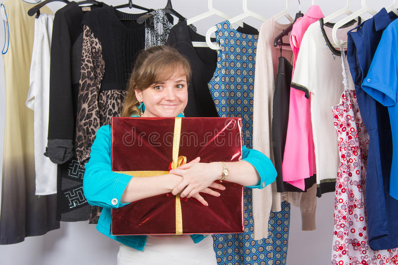 Happy young girl has received welcome gift in the background hang things on hangers royalty free stock images