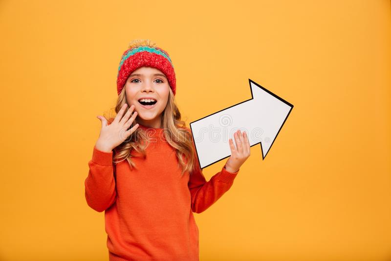 Happy Young girl in hat pointing with paper arrow away. Happy Young girl in sweater and hat pointing with paper arrow away and looking at the camera over orange royalty free stock images