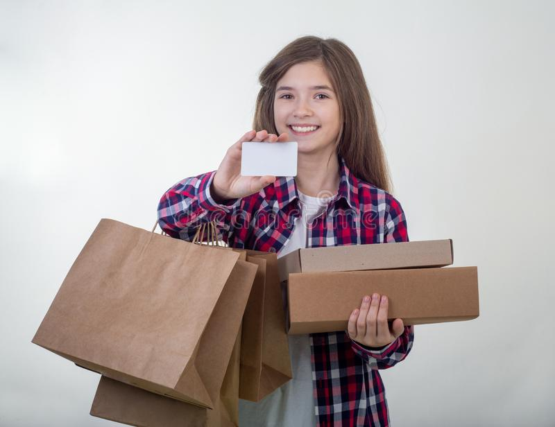 Happy young girl holding discount white card and shopping bags in her hands. Girl with credit card stock photography