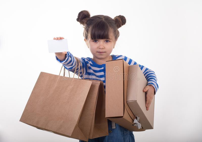Happy young girl holding discount white card and shopping bags in her hands. Kid with credit card. stock photos