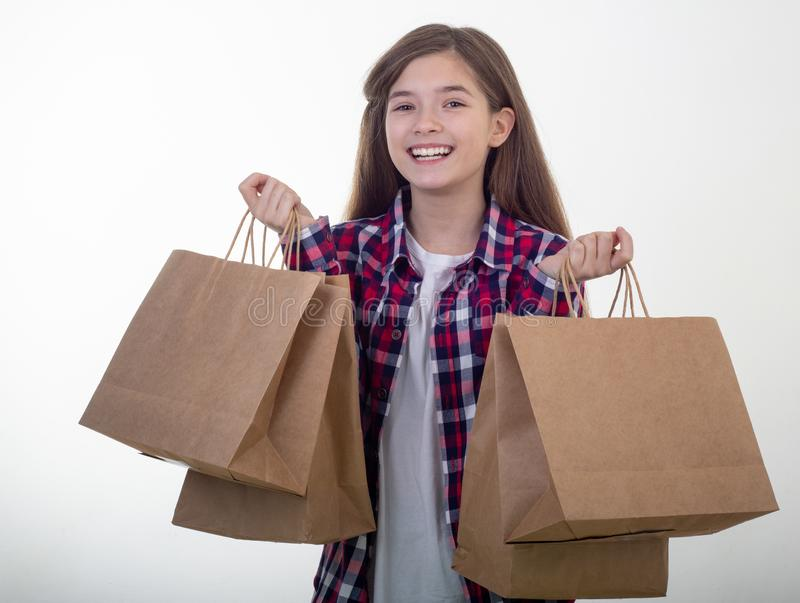 Happy young girl holding discount white card and shopping bags in her hands. Kid with credit card. royalty free stock photography