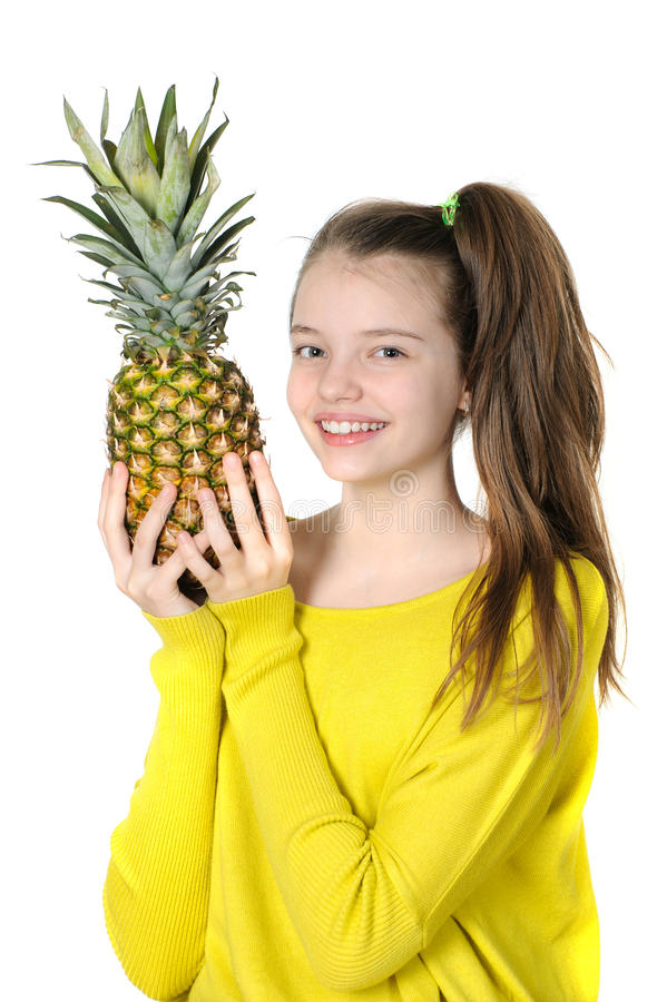 Happy young girl holding a large pineapple. stock photography