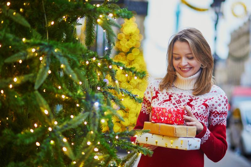 Happy young girl in holiday sweater with pile of Christmas presents royalty free stock photo