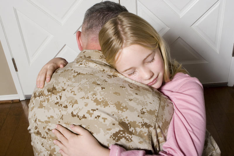 Happy young girl hugging her father in uniform. Young girl hugging her father in uniform stock photography