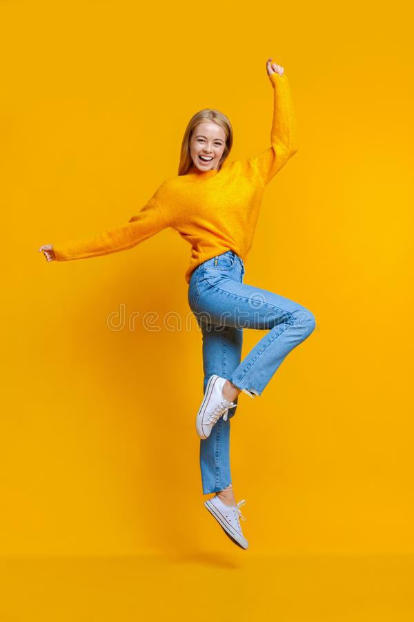 Free Happy Young Girl Jumping In Studio And Looking At Camera Stock Images - 161278144