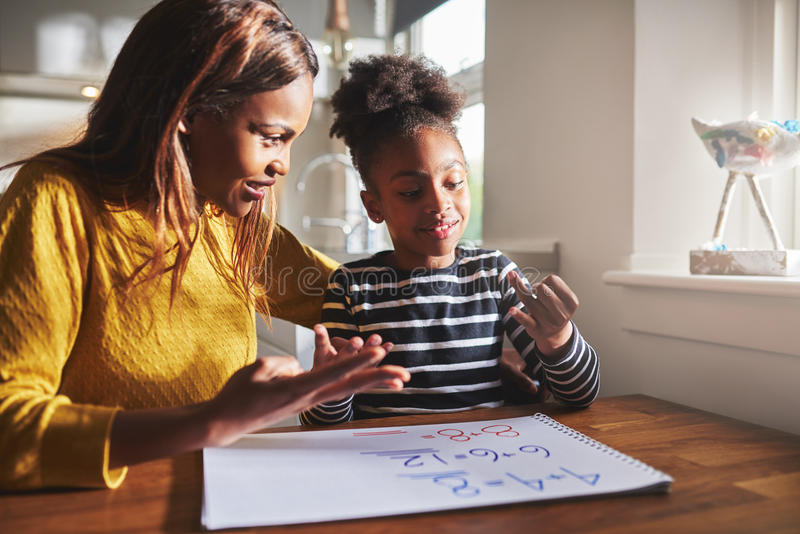 Happy young girl learning to calculate. With mother at home, black women and child royalty free stock images