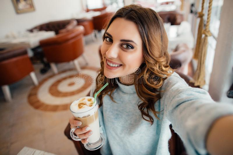Oung girl making self portrait with coffe in cafe stock photos