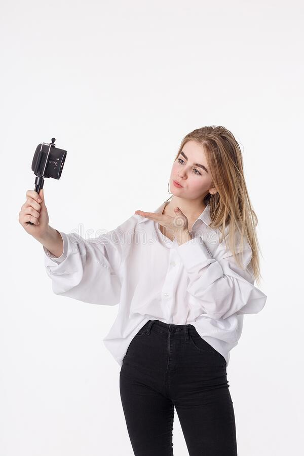 Happy young girl making self portrait with smartphone attached to small tripod royalty free stock photography